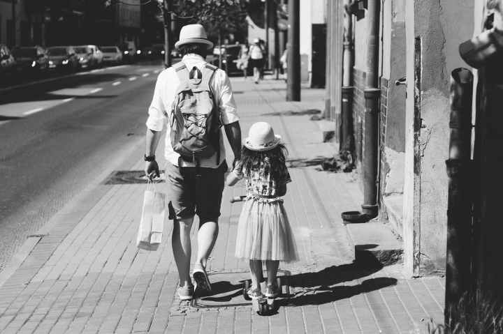 man holding girl while walking on street